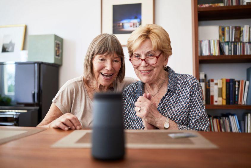 Two women look at a smart speaker excitedly.