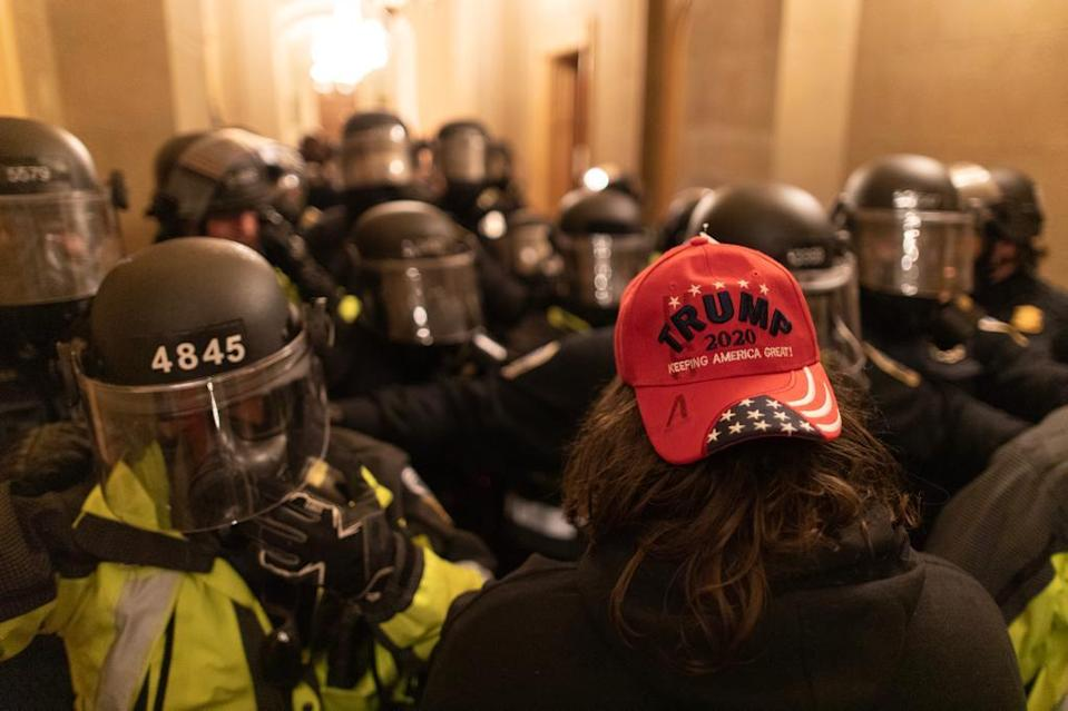 WASHINGTON D.C., USA - JANUARY 6: A US President Donald Trumps supporter faces off security forces after breaching security and entering the Capitol building in Washington D.C., United States on January 06, 2021. Pro-Trump rioters stormed the US Capitol as lawmakers were set to sign off Wednesday on President-elect Joe Biden's electoral victory in what was supposed to be a routine process headed to Inauguration Day. (Photo by Mostafa Bassim/Anadolu Agency via Getty Images)