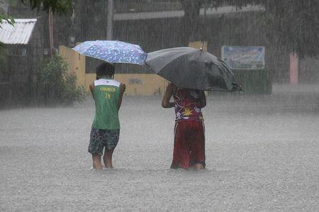 Residents wade across floodwaters caused by Typhoon Goni in Bacnotan, La Union, in northern Philippines August 22, 2015. REUTERS/TJ Corpuz