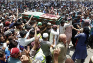 Supporters of Tehreek-e-Labiak Pakistan, a banned Islamist party, carry a casket of their colleague, who was killed in the Sunday's clash with police, for a funeral prayer, in Lahore, Pakistan, Monday, April 19, 2021. The outlawed Pakistani Islamist political group freed 11 policemen almost a day after taking them hostage in the eastern city of Lahore amid violent clashes with security forces, the country's interior minister said Monday. (AP Photo/K.M. Chaudary)
