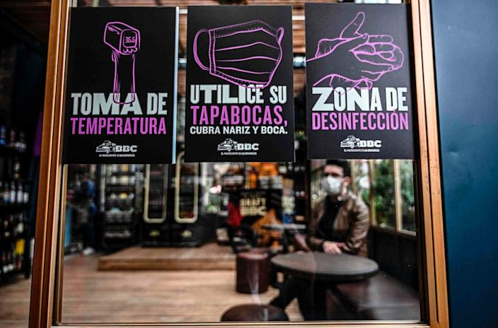 """Signs showing preventive measures against the spread of the coronavirus are displayed in a restaurant during a reopening pilot test in Bogota on July 10, 2020. <p class=""""copyright"""">Photo by JUAN BARRETO/AFP via Getty Images</p>"""