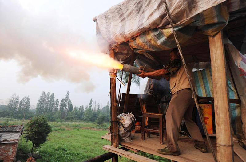 "In a picture taken on June 6, 2010 Chinese farmer Yang Youde fires his homemade cannon near his farmland on the outskirts of Wuhan, in central China's Hubei province. Yang's improvised cannons, which are made out of a wheelbarrow, pipes and fire rockets, are used to defend his fields against property developers who want his land. Land seizures have been a problem for years in China, and have given rise to the term ""nail house"" to describe a holdout tenant or occupant, likening them to a nail refusing to be hammered down. CHINA OUT AFP PHOTO (Photo credit should read STR/AFP via Getty Images)"