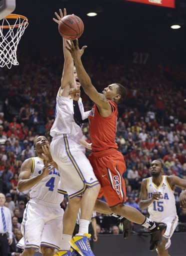 Arizona's Mark Lyons, right, goes up for a shot against UCLA's Travis Wear in the first half of a semifinal Pac-12 tournament NCAA college basketball game, Friday, March 15, 2013, in Las Vegas. (AP Photo/Julie Jacobson)