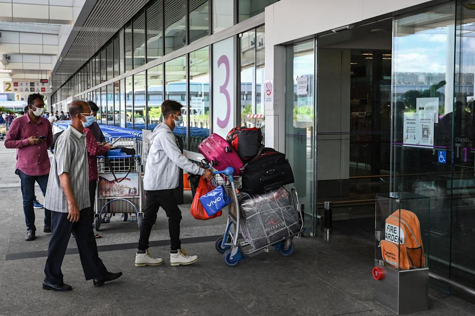 A traveller pushes his luggages on a trolley as he enters the departure hall at Changi International Airport in Singapore on August 19, 2021. (Photo by Roslan RAHMAN / AFP) (Photo by ROSLAN RAHMAN/AFP via Getty Images)