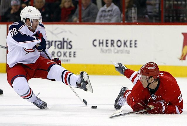 Carolina Hurricanes' Alexander Semin (28) of Russia, lies on the ice after colliding with Columbus Blue Jackets' Boone Jenner (38) during the first period of an NHL hockey game in Raleigh, N.C., Monday, Dec. 23, 2013. (AP Photo/Karl B DeBlaker)