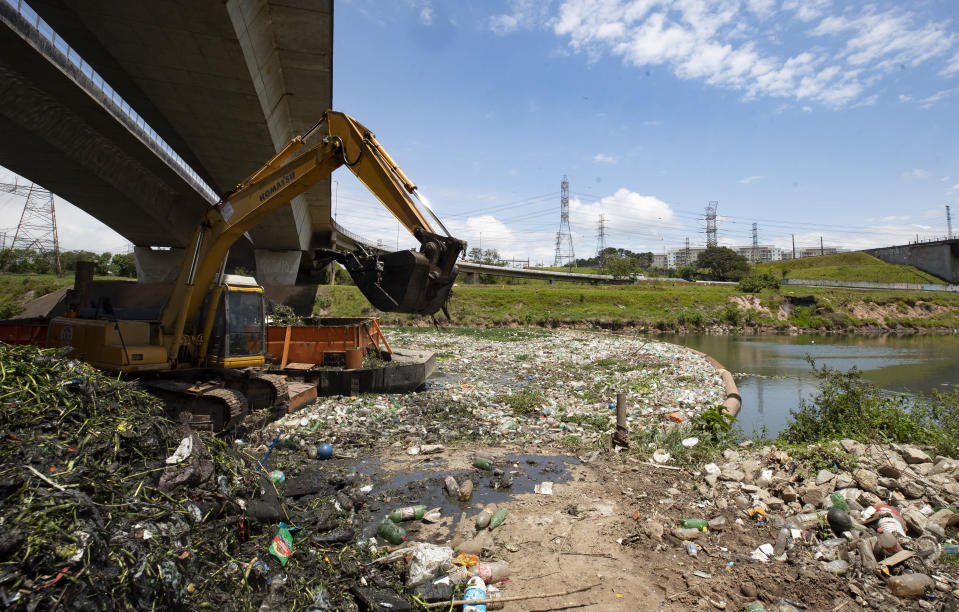 An excavator removes debris from the banks of the Pinheiros River in Sao Paulo, Brazil, Thursday, Oct. 22, 2020. Affected by domestic sewage and solid wastes discharges for years, Sao Paulo's state government is again trying to clean the Pinheiros River, considered one of the most polluted in Brazil. (AP Photo/Andre Penner)