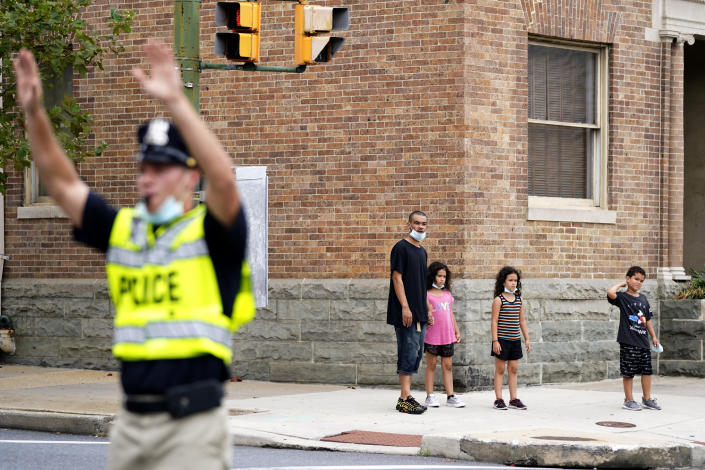 In this Sept. 9, 2020, photo pedestrians look on before crossing an intersection as a cadet in the Baltimore Police Academy directs traffic during an on the field class session in Baltimore. (AP Photo/Julio Cortez)