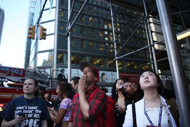 NEW YORK, NY - JUNE 12: People look up at broken scaffolding dangling from the top of the 46-story Hearst Tower moments after two trapped window washers were rescued on June 12, 2013 in New York City. The workers, who were servicing the window-washing equipment when the scaffolding broke, were left dangling 500 feet above Eighth Avenue. Firefighters and NYPD emergency service unit officers were were able to rescue the men as hundreds of onlookers gazed up from the street. (Photo by Spencer Platt/Getty Images)