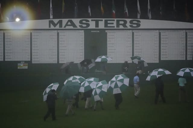 Official leave the Augusta National Golf Course after play was suspended