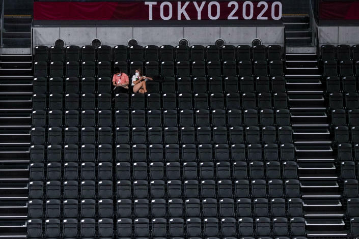 People sit in an empty tribune during a volleyball team training session at Ariake Arena at the 2020 Summer Olympics, Thursday, July 22, 2021, in Tokyo, Japan. (AP Photo/Manu Fernandez)