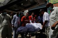 Rescue workers and relatives move a body of a victim, who was killed in a plane crash, in Karachi