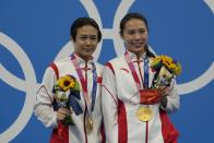Shi Tingmao and Wang Han pose for a photo after winning gold medals during the Women's Synchronized 3m Springboard Final at the Tokyo Aquatics Centre at the 2020 Summer Olympics, Sunday, July 25, 2021, in Tokyo, Japan. (AP Photo/Dmitri Lovetsky)