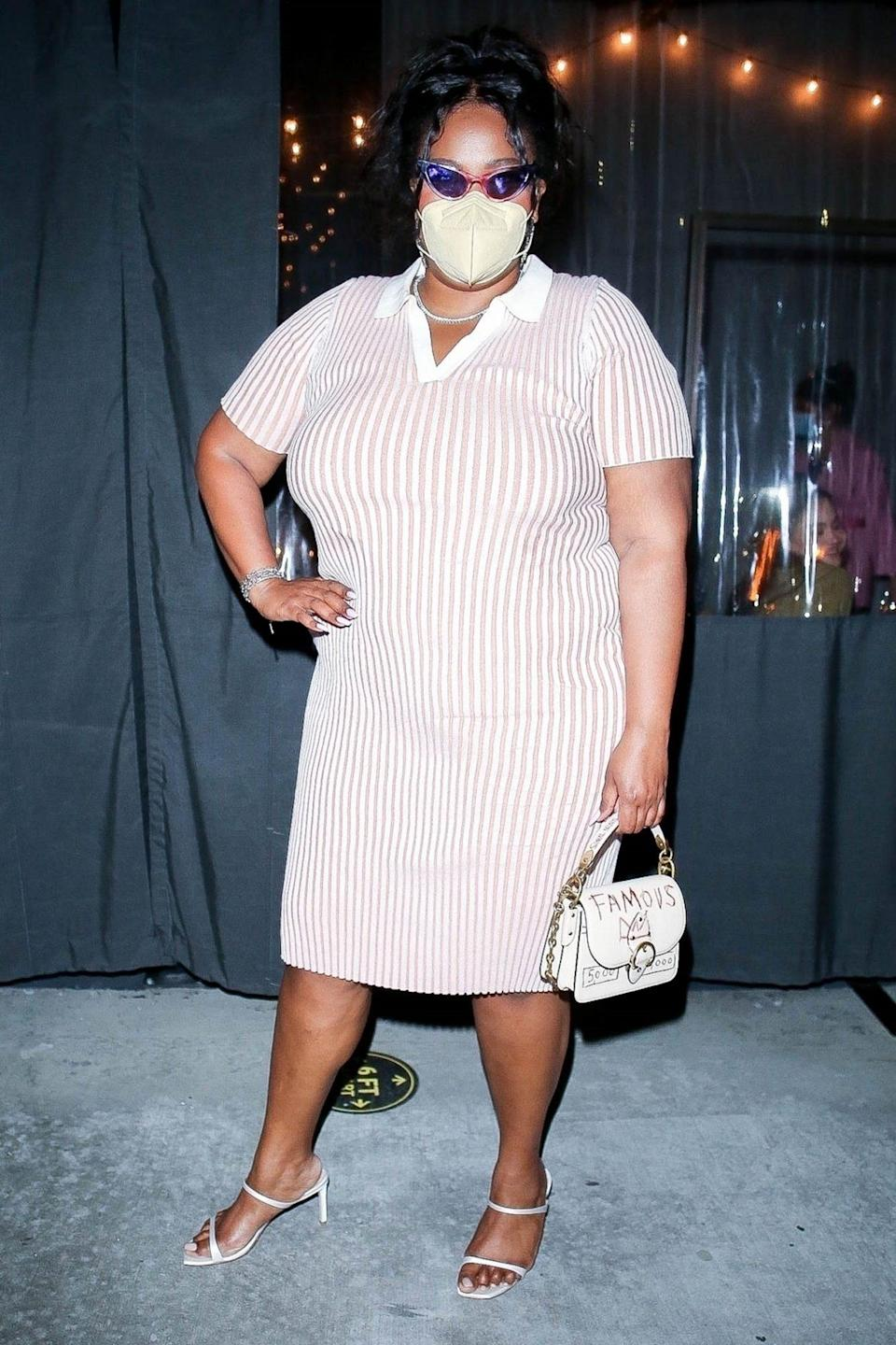 <p>Lizzo steps out in a striped dress and white sandals as she leaves dinner at Crossroads Kitchen in L.A. on Monday night. </p>