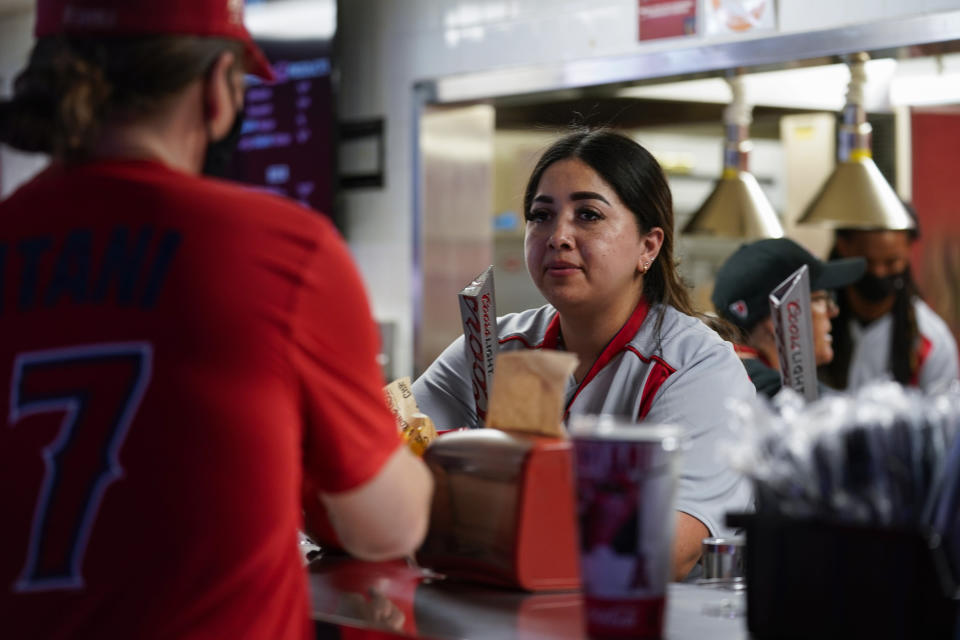 An employee of Angel Stadium serves a customer before a baseball game between the Boston Red Sox and the Los Angeles Angels Monday, July 5, 2021, in Anaheim, Calif. With baseball fans back in the stands and concessions being sold, ballpark employees have had a chance to return after the pandemic hit many of them hard. (AP Photo/Ashley Landis)