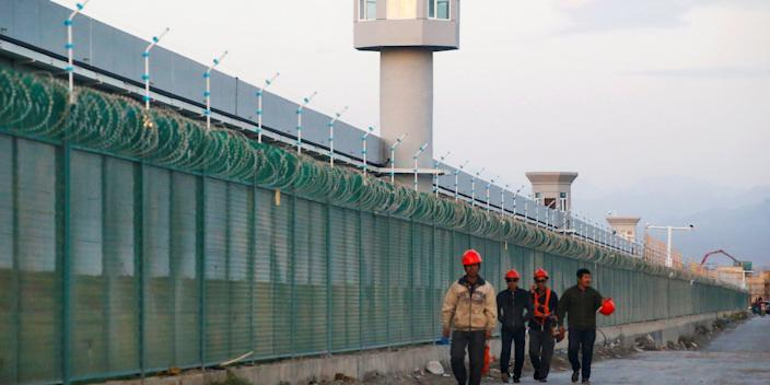 FILE PHOTO: Workers walk by the perimeter fence of what is officially known as a vocational skills education centre in Dabancheng in Xinjiang Uighur Autonomous Region, China September 4, 2018. REUTERS/Thomas Peter/File Photo