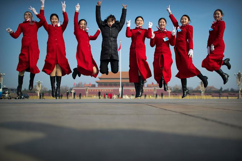 In this March 4, 2019, photo, bus ushers leap as they pose for a group photo during a meeting one day ahead of the opening session of China's National People's Congress (NPC) at the Great Hall of the People in Beijing. A year since removing any legal barrier to remaining China's leader for life, Xi Jinping appears firmly in charge, despite a slowing economy, an ongoing trade war with the U.S. and rumbles of discontent over his concentration of power. (AP Photo/Mark Schiefelbein, File)
