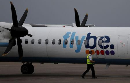 An airport worker examines a flybe aircraft before it takes off from Liverpool John Lennon Airport in Liverpool northern England.