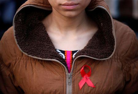 A participant with a red ribbon pin takes part in HIV/AIDS awareness campaign ahead of World Aids Day, in Kathmandu