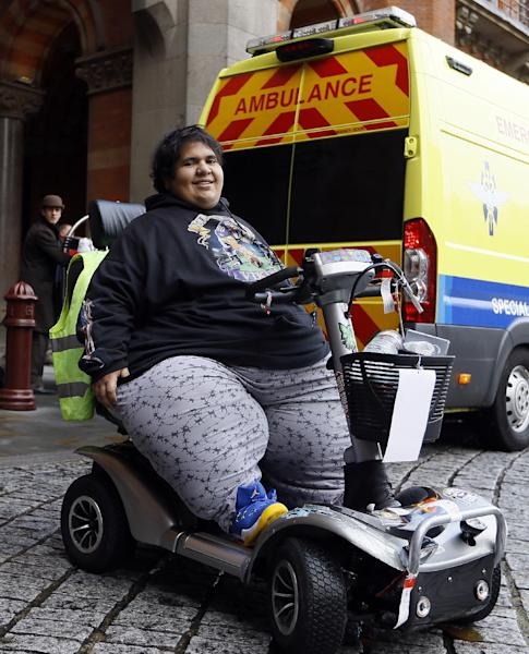 Kevin Chenais sits in his mobility scooter in front of an ambulance at St Pancras in London, Wednesday, Nov. 20, 2013. Kevin, who suffers from a medical condition will travel by ambulance and ferry back to France. (AP Photo/Kirsty Wigglesworth)