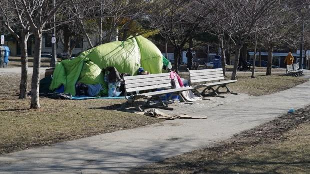 A cluster of tents sits behind some benches in Trinity Bellwoods Park.