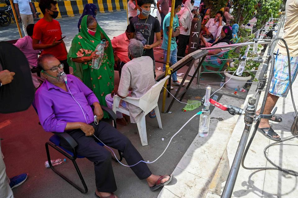 <p>Covid-19 coronavirus patients breathe with the help of oxygen provided by a Gurdwara, a place of worship for Sikhs, under a tent installed along the roadside in Ghaziabad, Uttar Pradesh</p> (AFP via Getty Images)
