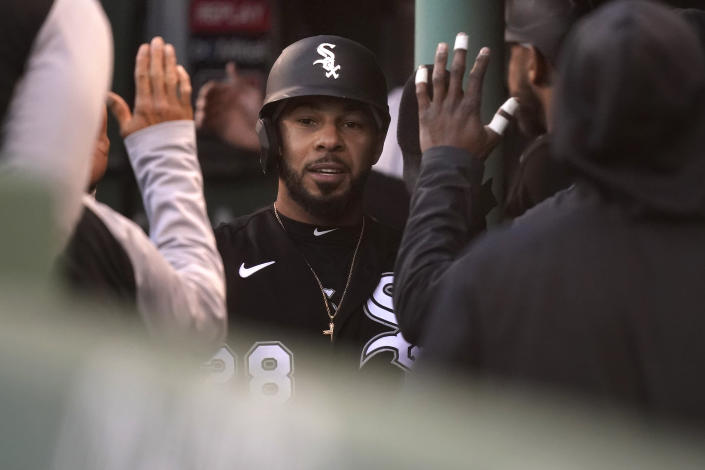 Chicago White Sox's Leury Garcia, center, is welcomed into the dugout after scoring on a sacrifice fly by Nick Madrigal in the sixth inning of a baseball game against the Boston Red Sox, Sunday, April 18, 2021, in Boston. The game is the second of a doubleheader Sunday. (AP Photo/Steven Senne)