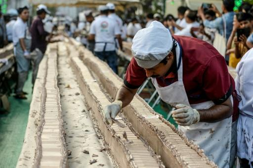 About 1,500 bakers and chefs prepared the serpentine dessert atop thousands of tables and desks