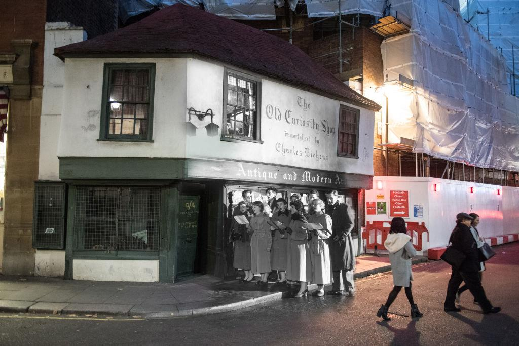 <p>Students of King's College sing Christmas carols outside the Old Curiosity Shop, as immortalised by Charles Dickens, on Portsmouth Street on 12 December, 1956 in London. (Getty) </p>