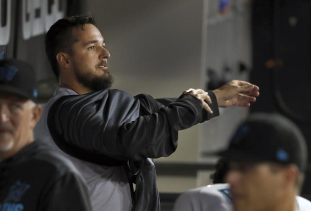 Miami Marlins starting pitcher Caleb Smith puts on his jacket in the dugout after losing a perfect game and no hitter during the sixth inning of a baseball game against the Chicago White Sox Tuesday, July 23, 2019, in Chicago. (AP Photo/Charles Rex Arbogast)