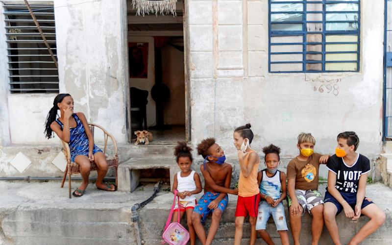 hildrens talk while wearing masks to protect themselves from the coronavirus pandemic in Havana, Cuba -  Yander Zamora/EPA-EFE/Shutterstock