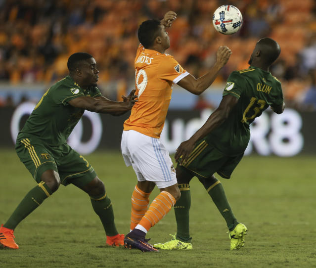 "<a class=""link rapid-noclick-resp"" href=""/soccer/teams/houston-dynamo/"" data-ylk=""slk:Houston Dynamo"">Houston Dynamo</a> forward <a class=""link rapid-noclick-resp"" href=""/soccer/players/mauro-manotas/"" data-ylk=""slk:Mauro Manotas"">Mauro Manotas</a> (19) battles with <a class=""link rapid-noclick-resp"" href=""/soccer/teams/portland-timbers/"" data-ylk=""slk:Portland Timbers"">Portland Timbers</a> players Larrys Mabiala (33) and Lawrence Olum (13) for possession of the ball during the MLS Western Conference semifinal soccer match Monday, Oct. 30, 2017, in Houston. (Yi-Chin Lee/Houston Chronicle via AP)"