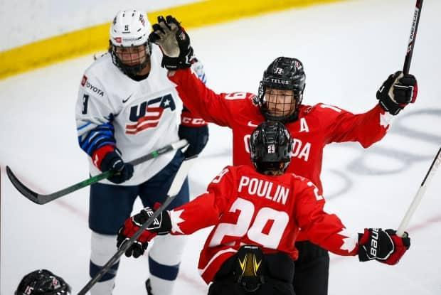 Canada's Brianne Jenner, right, celebrates her goal with teammate Marie-Philip Poulin, centre, in the second period of the gold medal final of the IIHF women's world championship on Tuesday in Calgary. (Jeff McIntosh/The Canadian Press - image credit)