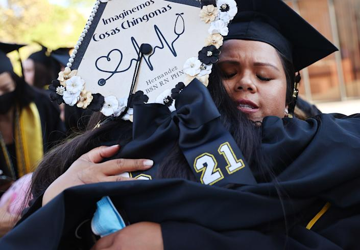 Cal State Los Angeles graduate Maricris Trask hugs another graduate following their commencement ceremony on July 27, 2021 in Los Angeles. (Photo by Mario Tama/Getty Images)