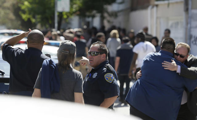 <p>San Francisco police in the foreground and UPS workers in the background stand outside a UPS package delivery warehouse where a shooting took place Wednesday, June 14, 2017, in San Francisco. A UPS spokesman says four people were injured in the shooting at the facility and that the shooter was an employee. (AP Photo/Eric Risberg) </p>
