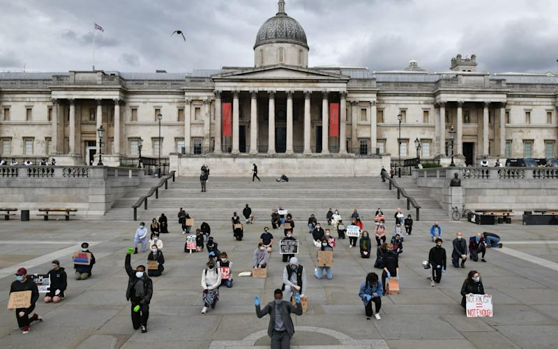 """Protesters employing social distancing """"take a knee"""" as they attend a demonstration in Trafalgar Square in central London on June 5, 2020, to show solidarity with the Black Lives Matter movement in the wake of the killing of George Floyd - Dominic Lipinski/PA"""