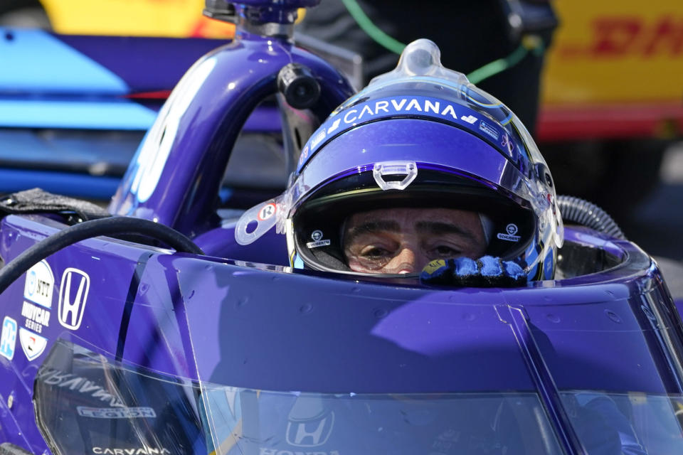 Jimmie Johnson climbs out of his car following practice for the IndyCar auto race at Indianapolis Motor Speedway, Friday, May 14, 2021, in Indianapolis. (AP Photo/Darron Cummings)