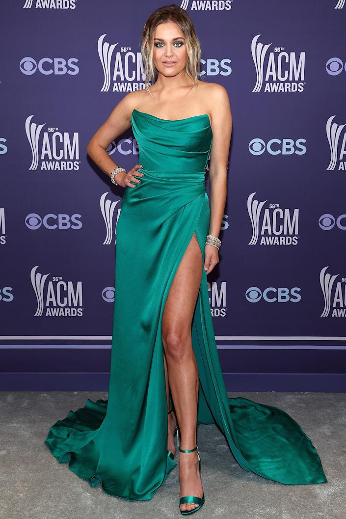 <p>goes glam in a strapless green Dolce & Gabbana gown with thigh-high slit and matching green heels. </p>