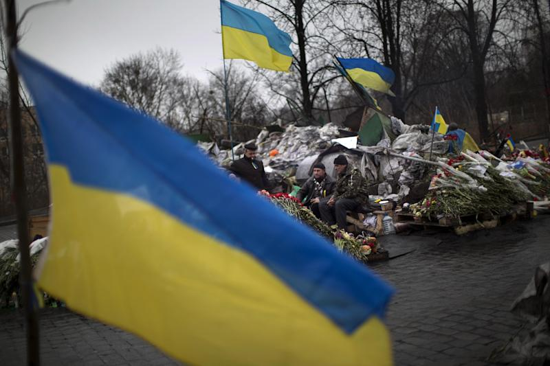 """Anti-Yanukovych protesters guard a barricade on a street heading to Kiev's Independence Square, in Ukraine, Wednesday, March 5, 2014. Stepping back from the brink of war, Vladimir Putin talked tough but cooled tensions in the Ukraine crisis Tuesday, saying Russia has no intention """"to fight the Ukrainian people"""" but reserves the right to use force. As the Russian president held court in his personal residence, U.S. Secretary of State John Kerry met with Kiev's fledgling government and urged Putin to stand down. (AP Photo/Emilio Morenatti)"""