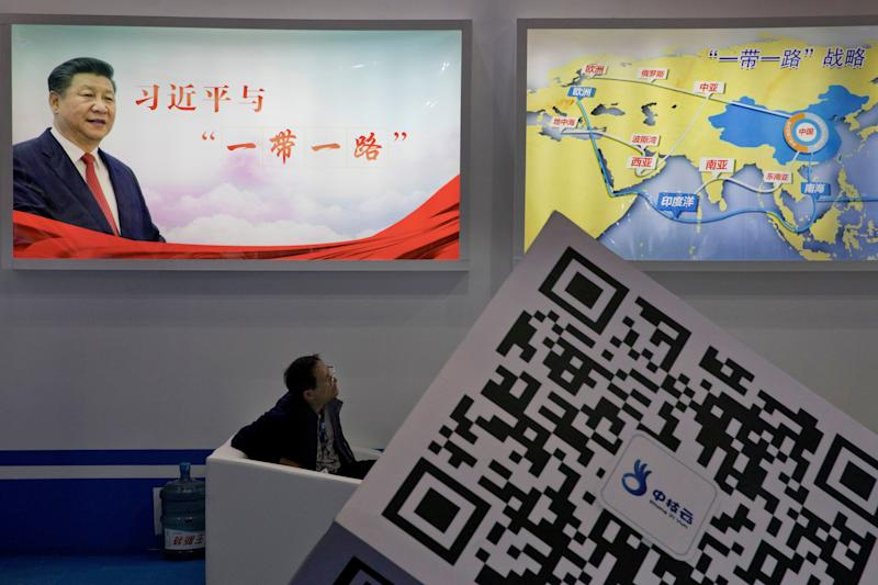"In this April 28, 2017 photo, an attendee at a conference looks up near a portrait of Chinese President Xi Jinping with the words ""Xi Jinping and One Belt One Road"" and ""One Belt One Road strategy,"" in Beijing. China will seek to burnish President Xi Jinping's stature as a world-class statesman at an international gathering centered on his signature foreign policy effort envisioning a future world order in which all roads lead to Beijing. The ""Belt and Road Forum"" opening Sunday, May 14 is the latest in a series of high-profile appearances aimed at projecting Xi's influence on the global stage ahead of a key congress of the ruling Communist Party later this year. (AP Photo/Ng Han Guan)"