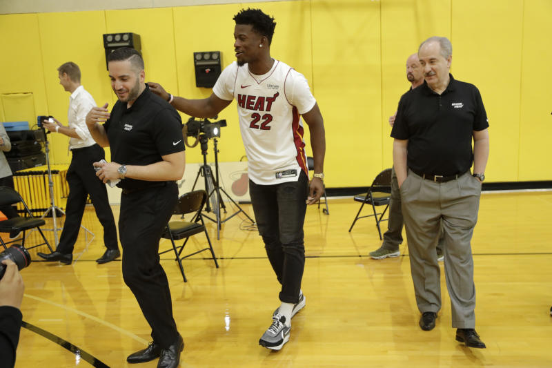 Miami Heat guard Jimmy Butler (22) jokes with Heat staff following an NBA basketball news conference, Friday, Sept. 27, 2019, in Miami. Butler spoke publicly for the first time since the July trade that brought him to South Florida as the new face of the franchise. (AP Photo/Lynne Sladky)
