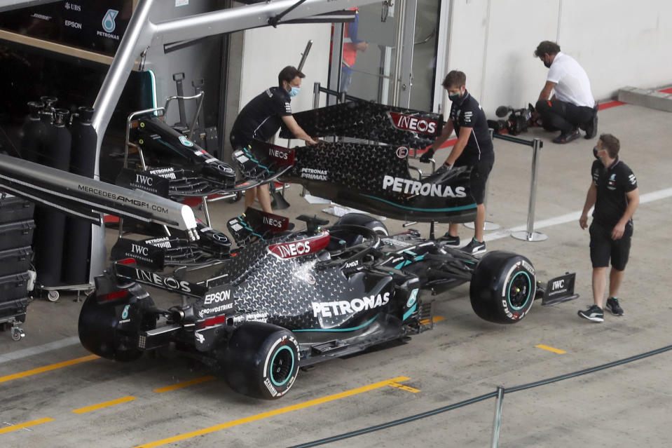 Mercedes technicians work around Lewis Hamilton's car the at the Red Bull Ring racetrack in Spielberg in Spielberg, Austria, Thursday, July 2, 2020. Austrian Formula One Grand Prix will be held on Sunday. (AP Photo/Darko Bandic)
