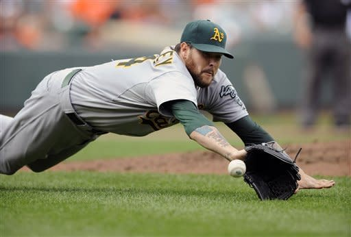 Oakland Athletics starting pitcher Travis Blackley dives to field a ball that went for a bunt single by Baltimore Orioles' Omar Quintanilla during the third inning of a baseball game, Sunday, July 29, 2012, in Baltimore. (AP Photo/Nick Wass)