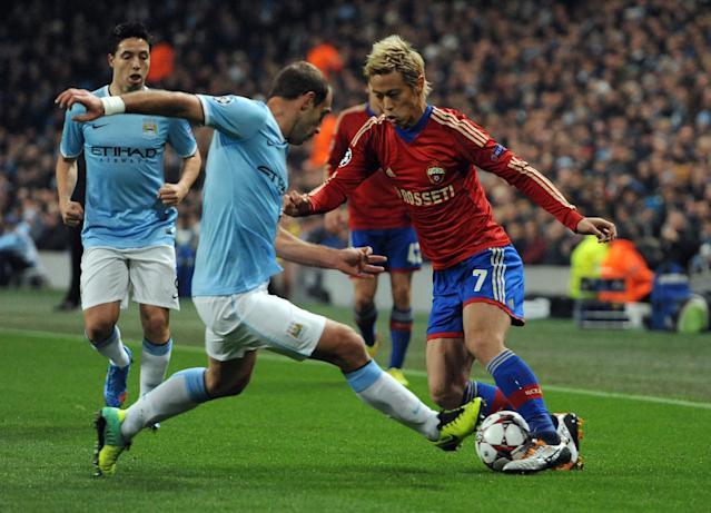 Manchester City's Pablo Zabaleta, left, tackles CSKA Moscow's Keisuke Honda during the Champions League Group D soccer match at the Etihad Stadium in Manchester, England, Tuesday, Nov. 5, 2013. (AP Photo/Clint Hughes)