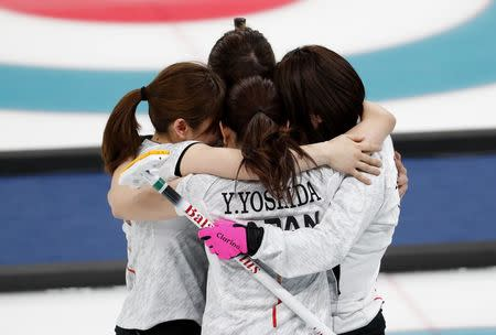Curling - Pyeongchang 2018 Winter Olympics - Women's Bronze Medal Match - Britain v Japan - Gangneung Curling Center - Gangneung, South Korea - February 24, 2018 - Japan's curlers embrace after winning the match. REUTERS/Cathal McNaughton