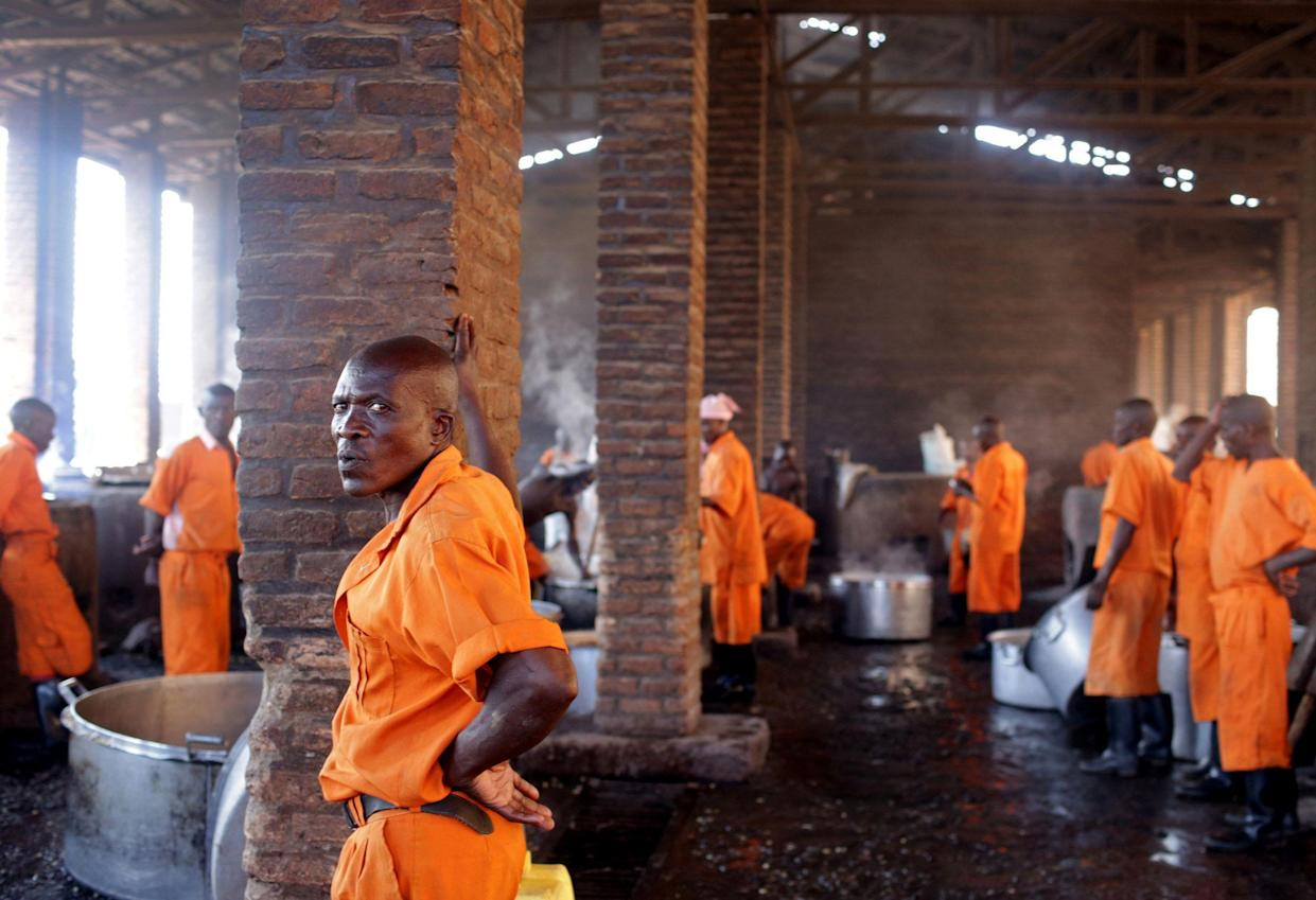 Prisoners rest in between cooking food via peat and biogas at Rwamagana Prison in Rwamagana, Rwanda, on November 18, 2017. All of Rwanda's prisons use their prisoners' waste - in addition to that of cows - to fuel their kitchens via biogas. At Rwamagana, biogas is used to cook corn, and peat cooks rice and beans. Many prisoners say they can usually tell when biogas is used due to the lack of smokey flavor in food. (Photograph by Yana Paskova)