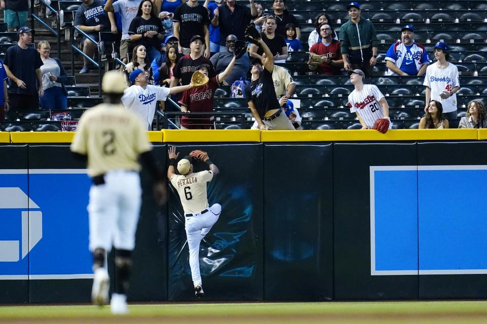 Arizona Diamondbacks left fielder David Peralta (6) and shortstop Geraldo Perdomo (2) watch fans reach for a home run hit by Los Angeles Dodgers' Trea Turner during the first inning of a baseball game Sunday, Sept. 26, 2021, in Phoenix. (AP Photo/Ross D. Franklin)