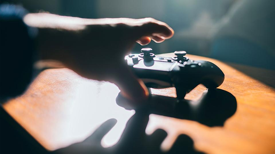 Pictured is a person's hand reaching for a game controller.