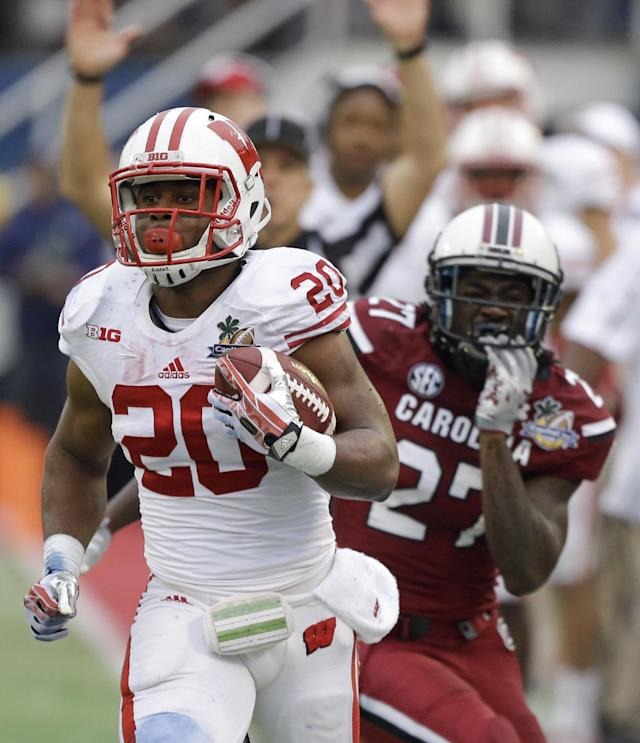 Wisconsin running back James White (20) gets past South Carolina cornerback Victor Hampton (27) for a short gain during the first half of the Capital One Bowl NCAA college football game in Orlando, Fla., Wednesday, Jan. 1, 2014.(AP Photo/John Raoux)