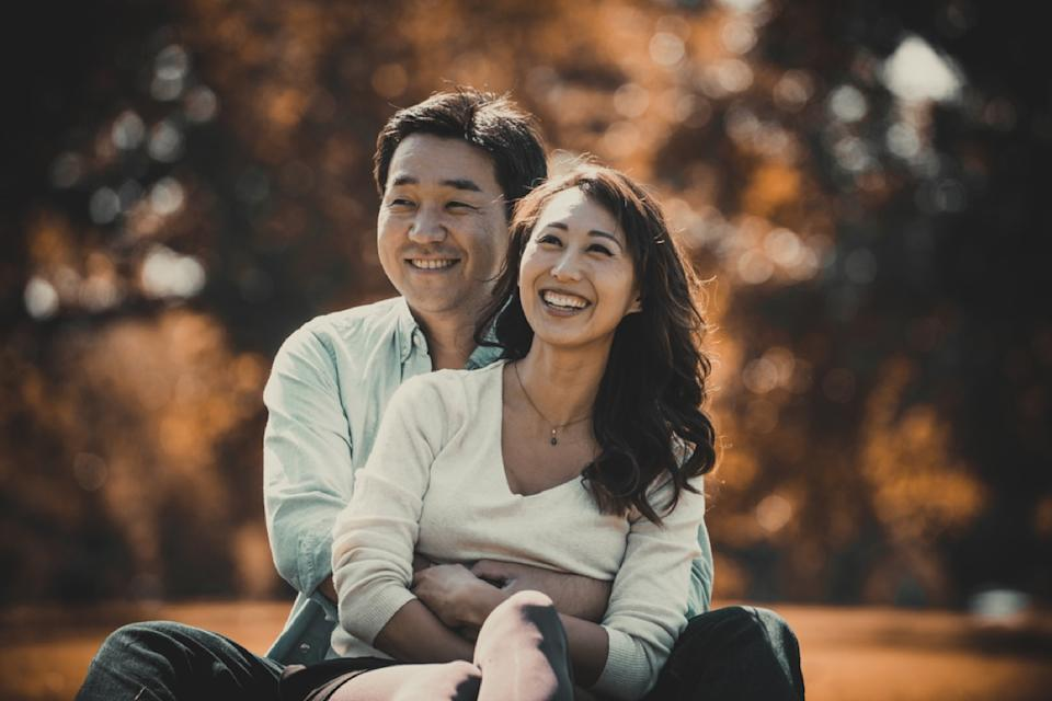 middle aged asian couple holding each other outside