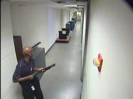 Aaron Alexis moves through the hallways of Building #197 carrying a Remington 870 shotgun in this undated handout photo released by the FBI